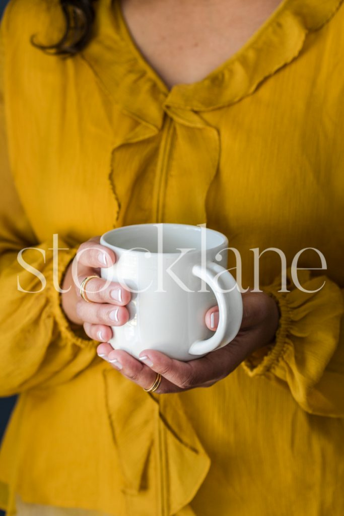 Vertical stock photo of a woman holding a coffee cup.