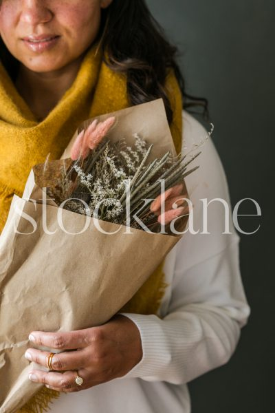 Vertical stock photo of a woman holding a dried fall bouquet.