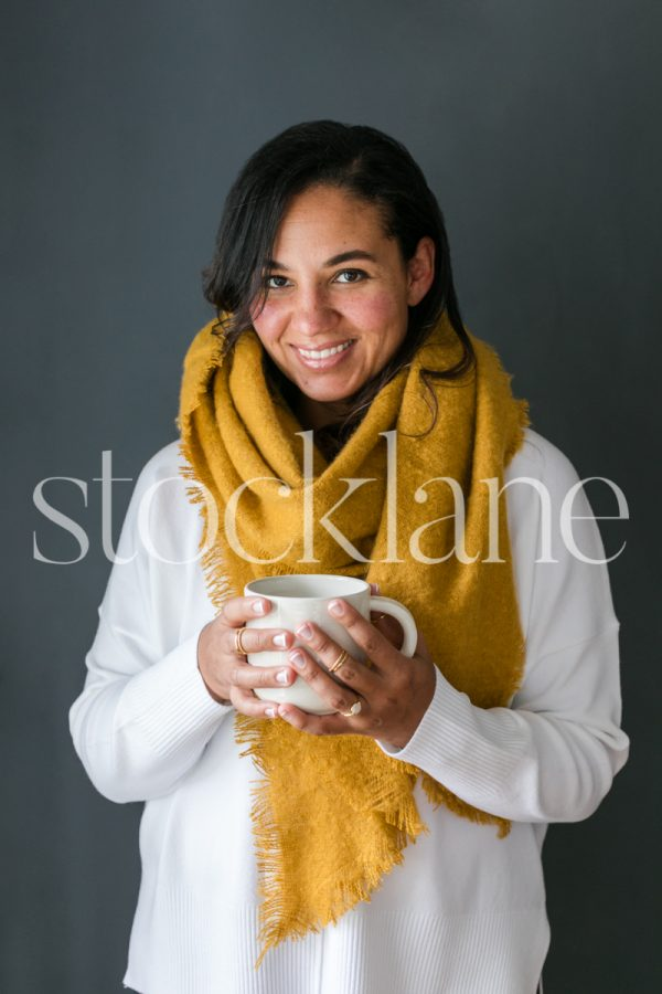Vertical stock photo of a woman holding a cup of coffee.