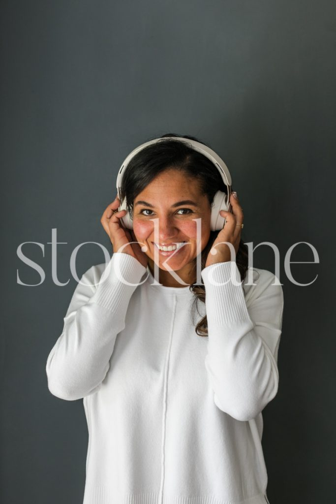 Vertical stock photo of woman with headphones.