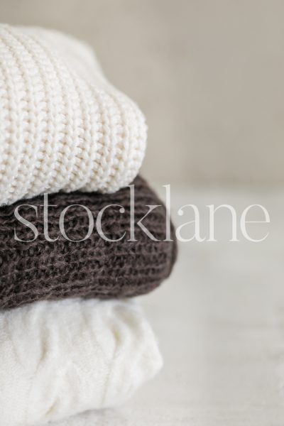 Vertical stock photo of neutral colored sweaters.