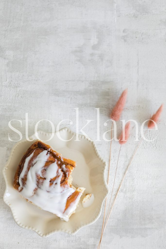 Vertical stock photo of a cinnamon roll on a white background.