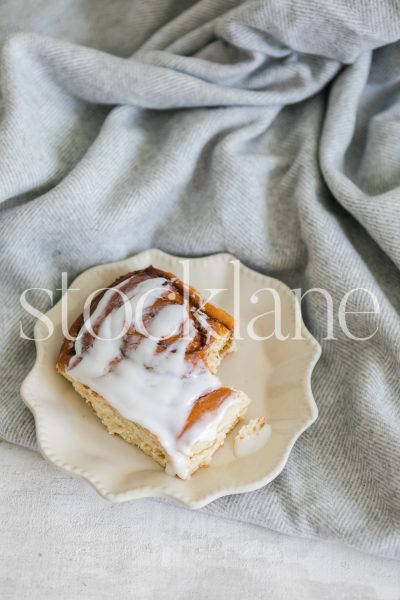 Vertical stock photo of a cinnamon roll on a gray blanket.