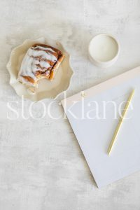 Vertical stock photo of a white desktop and a cinnamon roll.