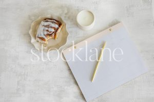 Horizontal stock photo of a white desktop and a cinnamon roll.