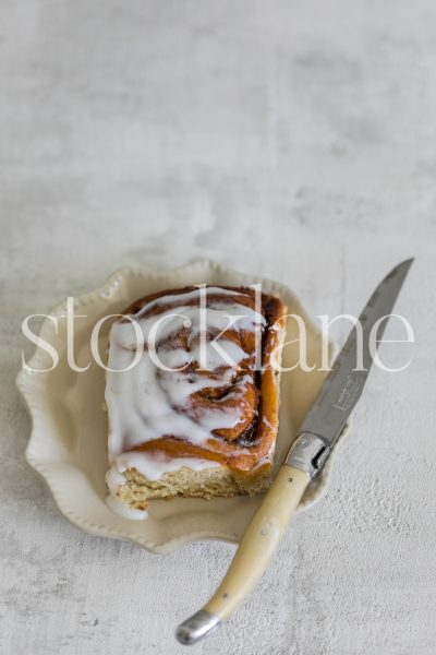 Vertical stock photo of a cinnamon roll on a vintage plate.