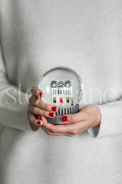Vertical stock photo of a woman holding a holiday snow globe.