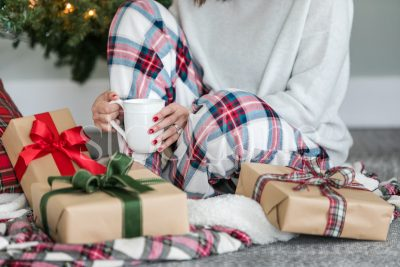 Horizontal stock photo of woman sitting next to Christmas presents.