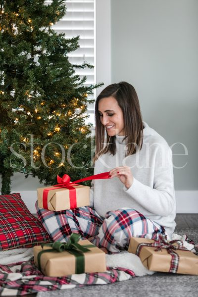 Vertical stock photo of a woman opening a gift on Christmas morning.