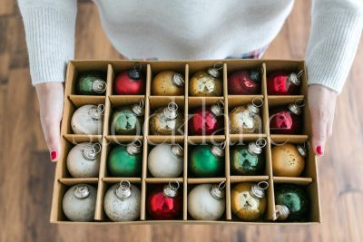 Horizontal stock photo of a woman holding a box of Christmas ornaments.