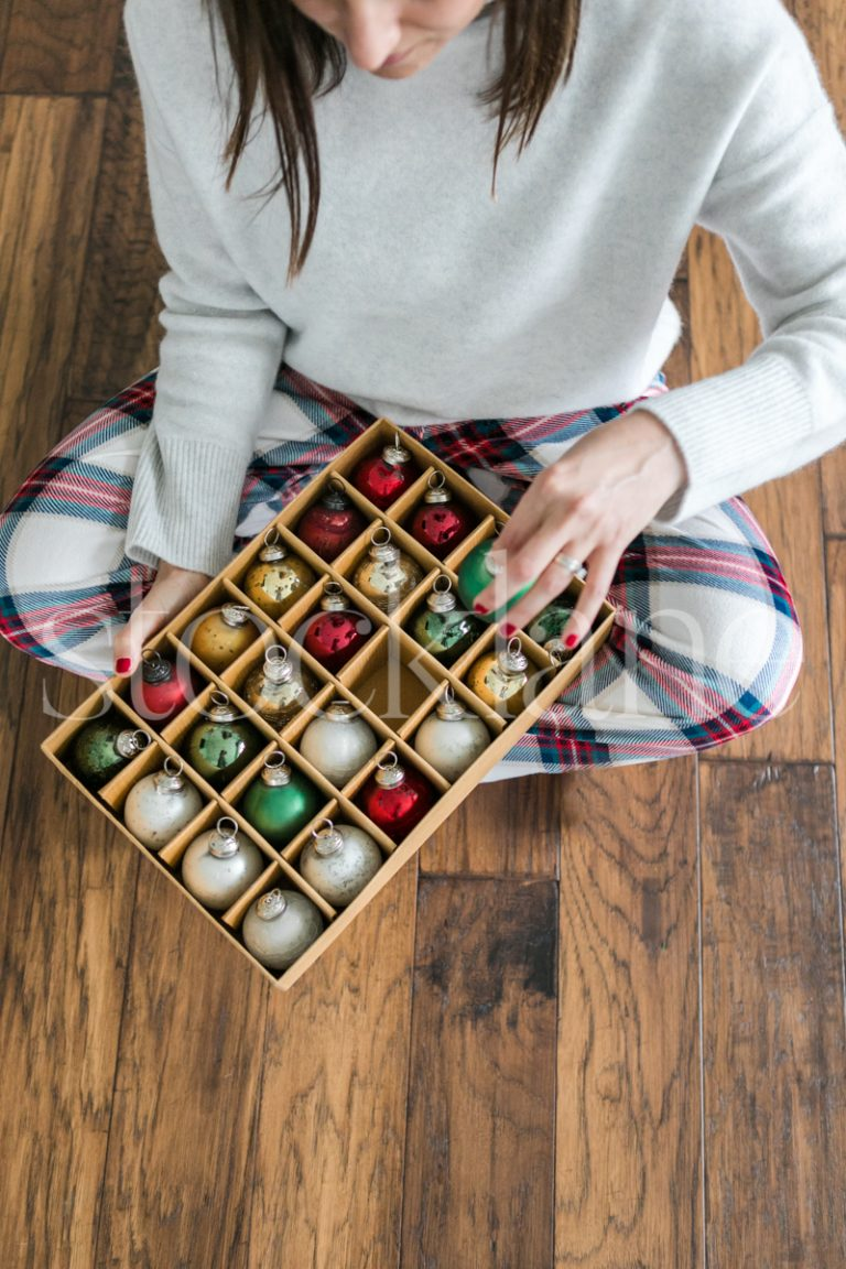 Vertical stock photo of a woman holding a box of Christmas ornaments.