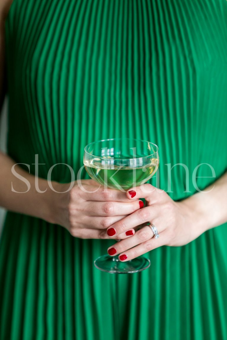 Vertical stock photo of a woman in a green dress holding a glass of champagne.