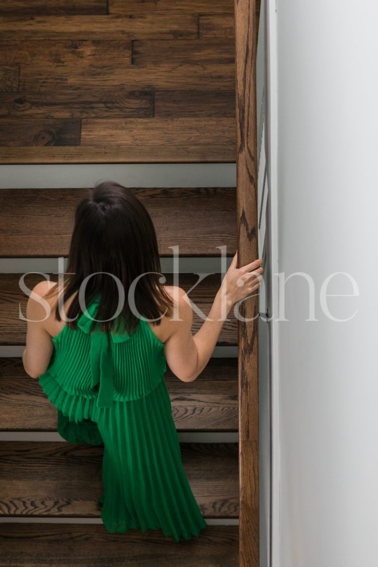 Vertical stock photo of a woman in a green dress going up stairs.