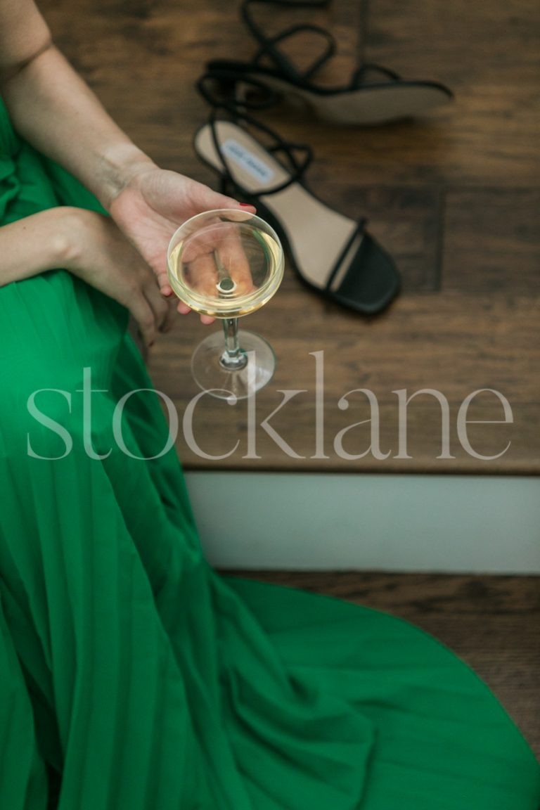 Vertical stock photo of a woman in a green dress sitting on stairs, holding a glass of champagne.