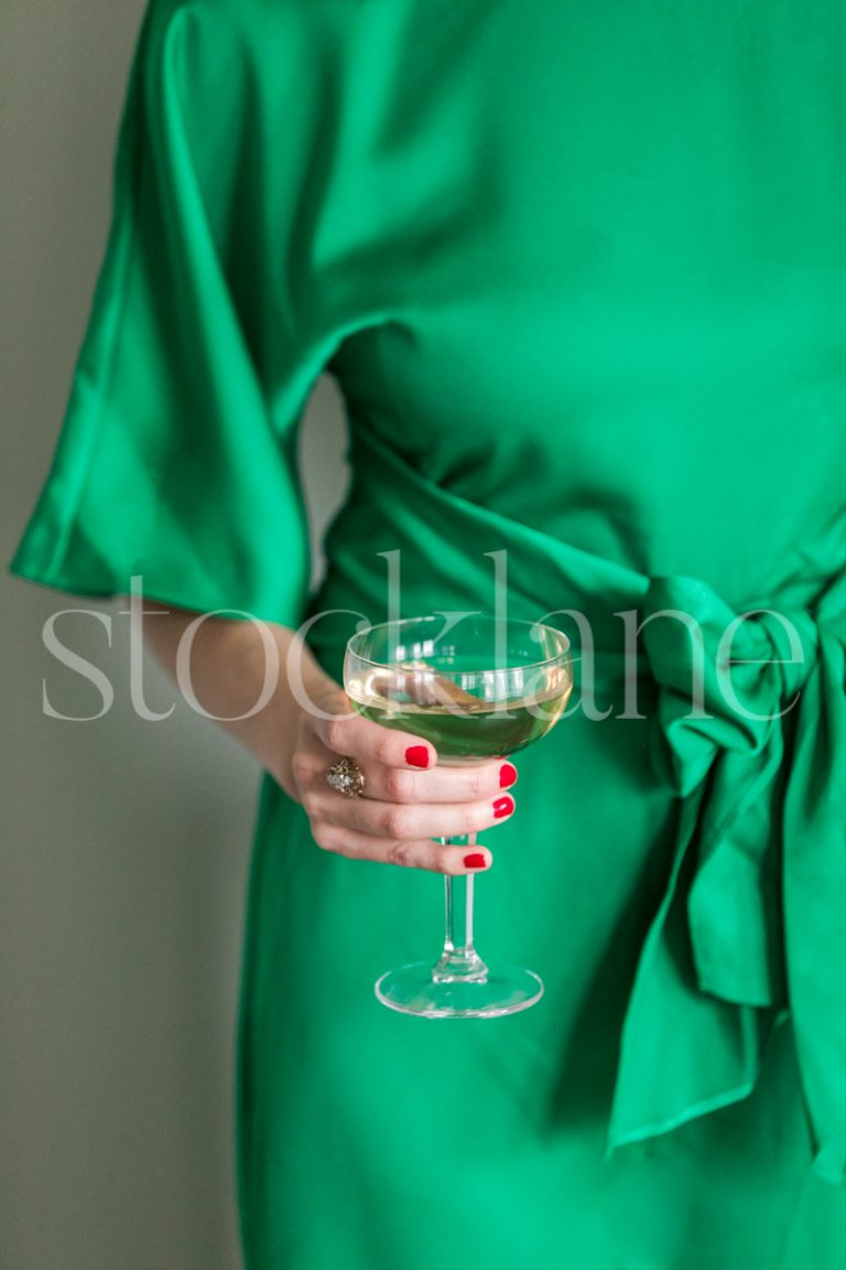 Vertical stock photo of a woman wearing a green dress holding a glass of champagne.