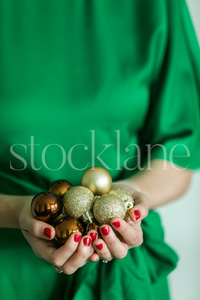 Vertical stock photo of woman holding gold ornaments