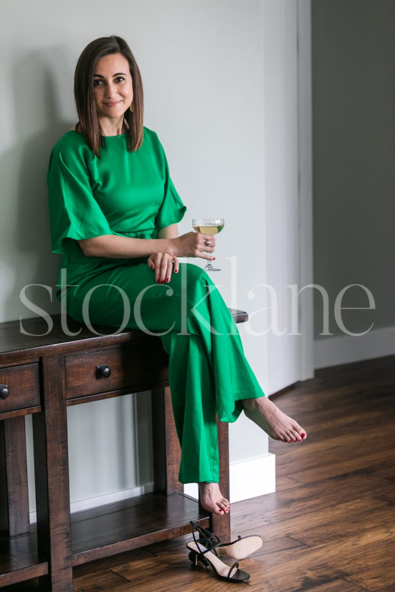 Vertical stock photo of a woman in a green outfit holding a glass of champagne.