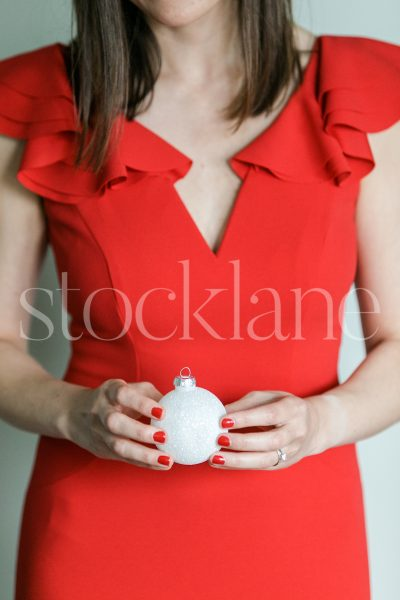 Vertical stock photo of a woman in a red dress holding a Christmas ornament.