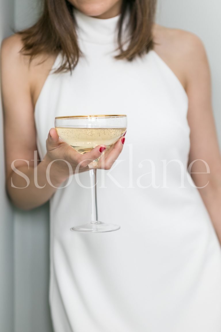 Vertical stock photo of a woman in a white dress holding a glass of champagne.