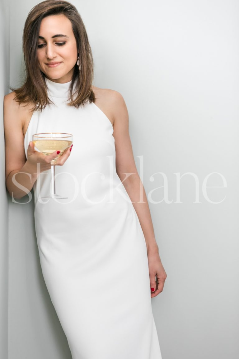 Vertical stock photo of a woman in a white dress holding a glass of champagne