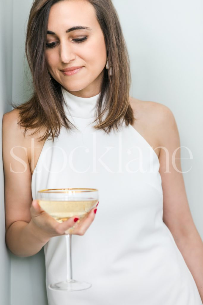 Vertical stock photo of a women in a white dress holding a glass of champagne
