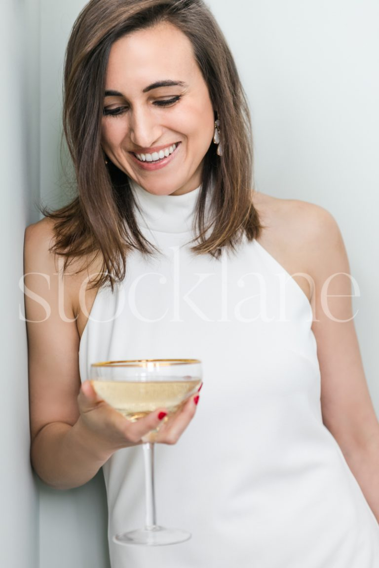 Vertical Stock photo of a woman in a white dress with a glass of champagne