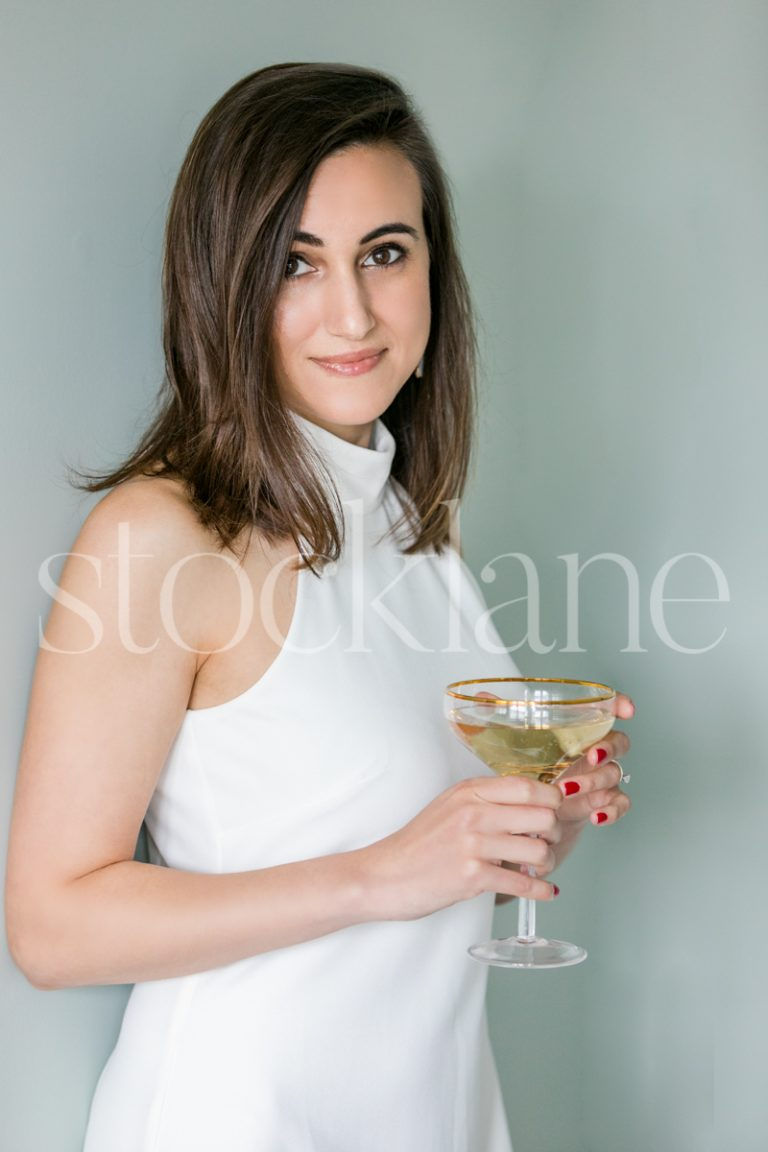 Vertical Stock photo of a women in a white dress with a glass of champagne