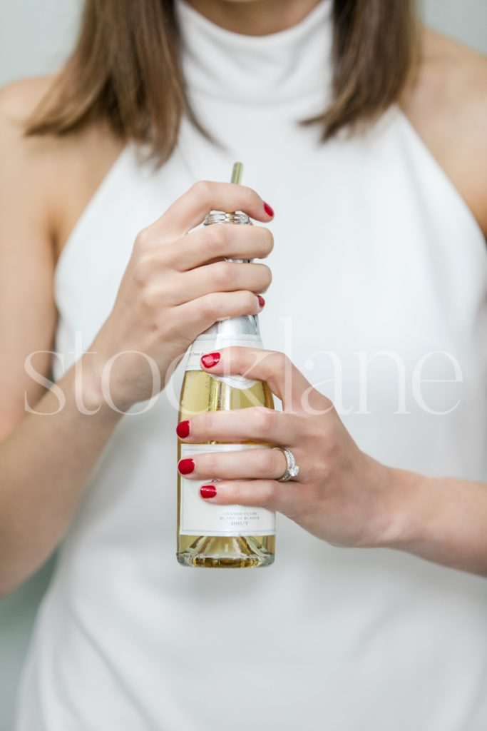 Vertical stock photo of a woman in a white dress with a drink