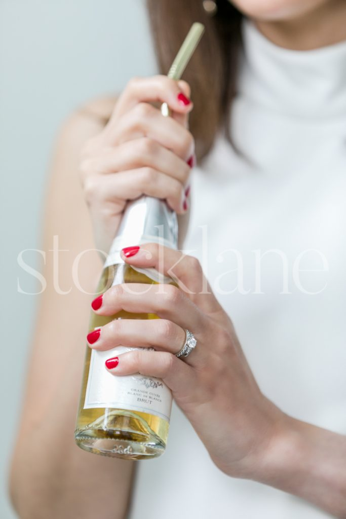 Vertical stock photo of a a woman in a white dress with a bottle of champagne