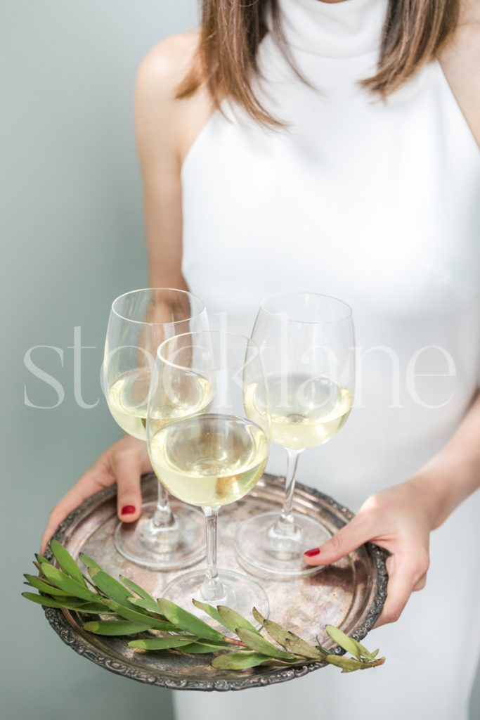 Vertical stock photo of a woman in a white dress with a tray of wine glasses