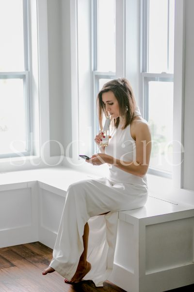 Vertical stock photo of a woman in a white dress holding a bottle of champagne
