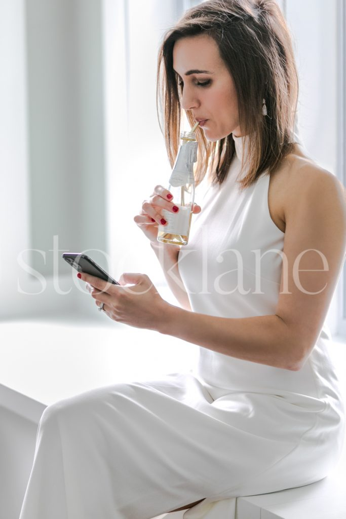 Vertical stock photo of a woman in a white dress with a bottle of champagne