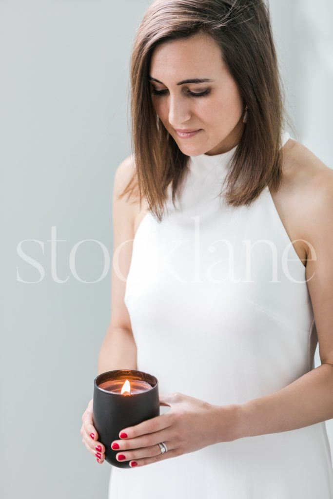 Vertical stock photo of a woman in a white dress with a candle