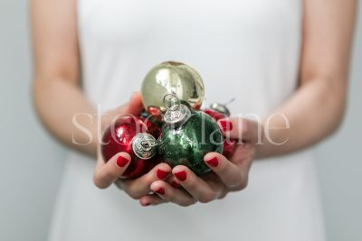 Horizontal stock photo of a woman in white dress with Christmas ornaments