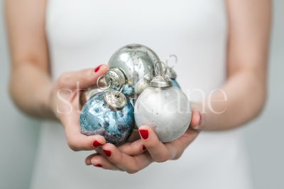 Horizontal Stock photo of a woman in a white dress with Christmas ornaments