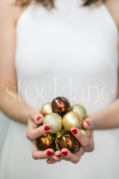 Vertical Stock photo of a woman in a white dress with Christmas ornaments