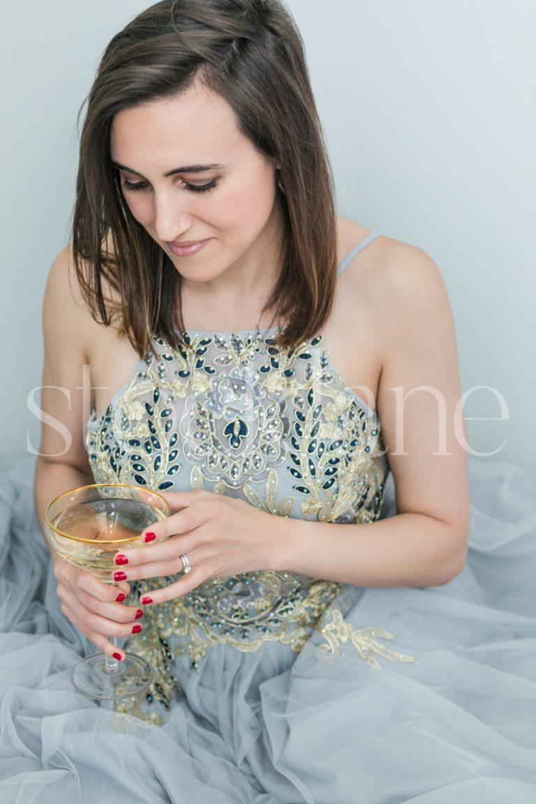 Vertical stock photo of a woman in a light blue dress with a glass of Champagne