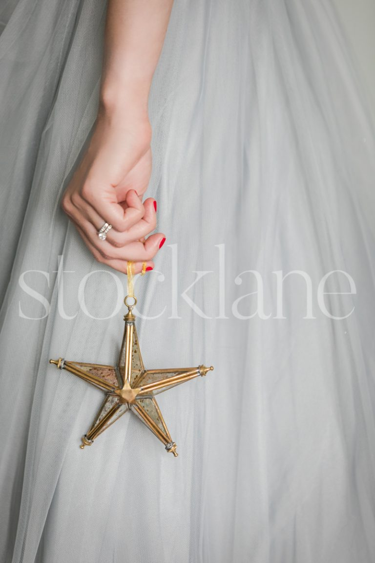 Vertical stock photo of a woman in a light blue dress with a Christmas ornament