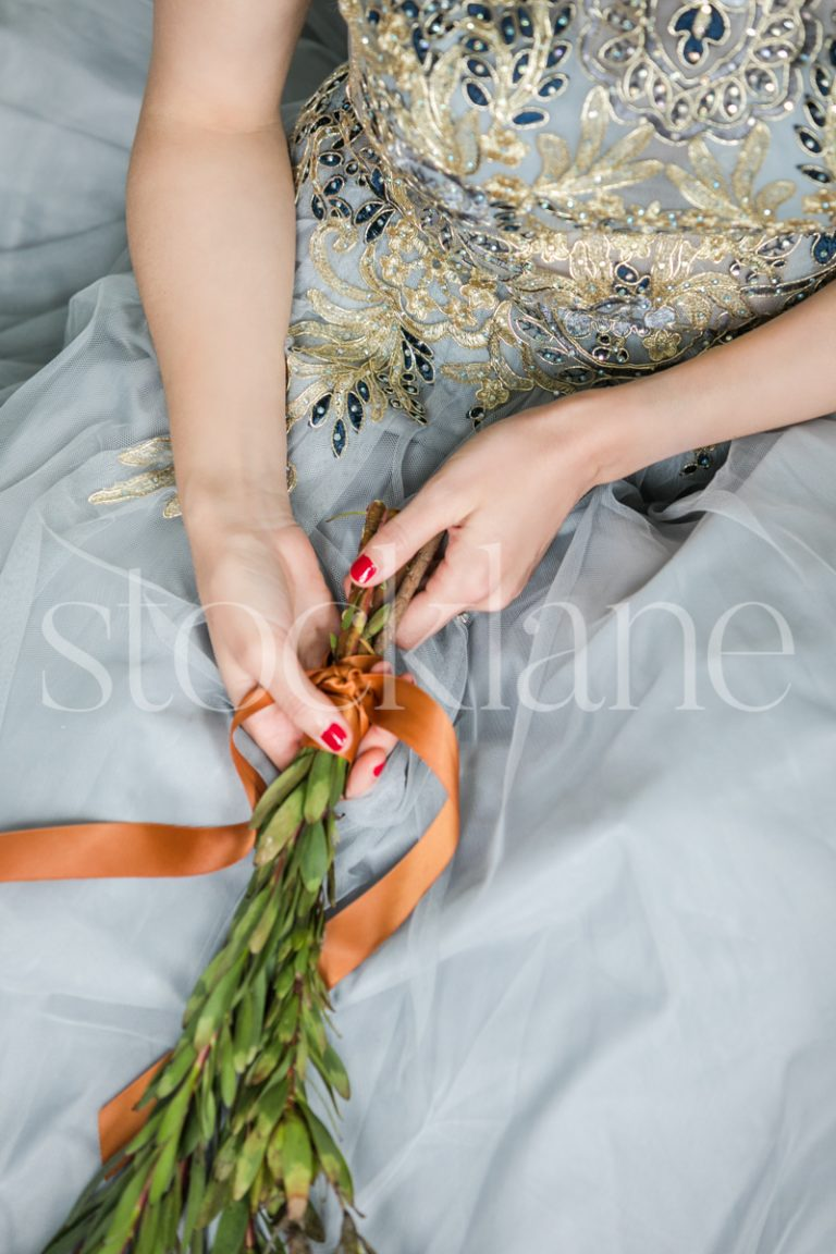 Vertical stock photo of a woman in a light blue dress with Christmas greenery
