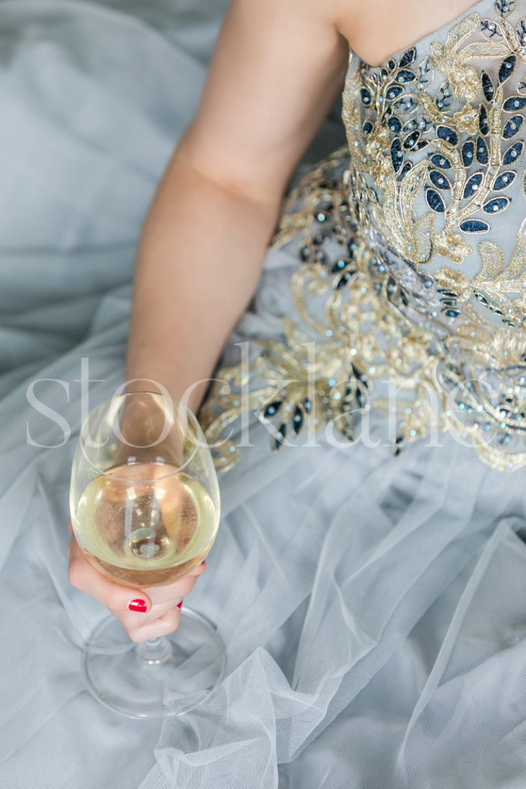 Vertical stock photo of a woman in a light blue dress with a glass of wine