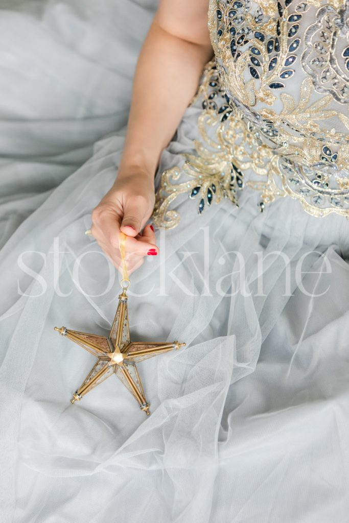 Vertical Stock photo of a woman in a white dress with a Christmas ornament