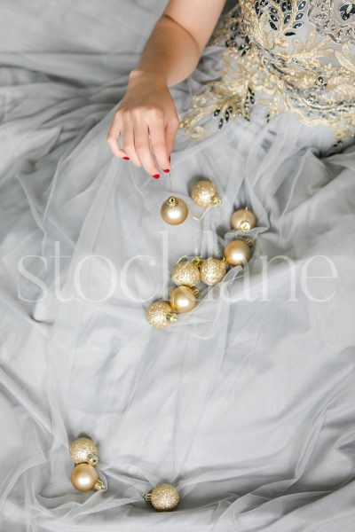 Vertical stock photo of a woman in a light blue dress with Christmas ornaments