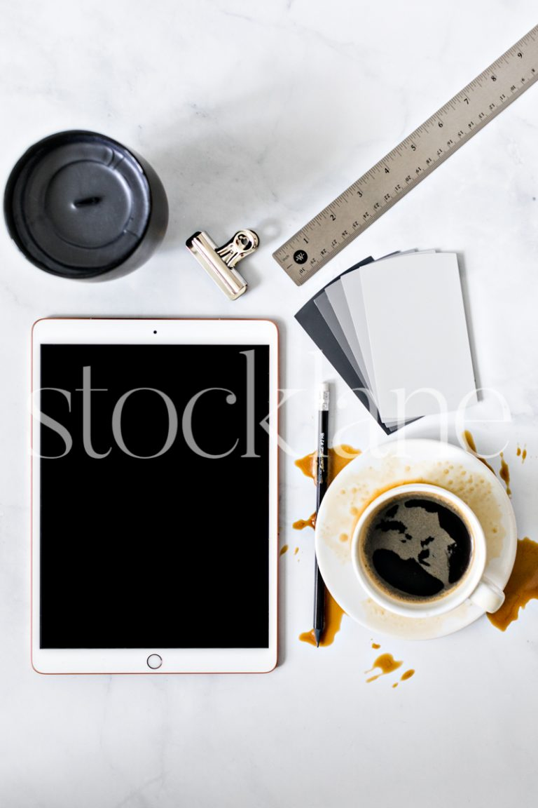 Vertical stock photo of desktop with iPad and coffee