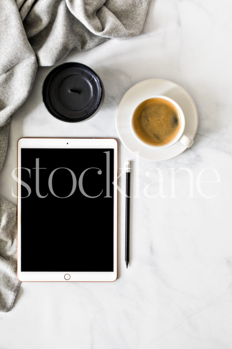 Vertical stock photo of a desktop with an iPad and a cup of coffee