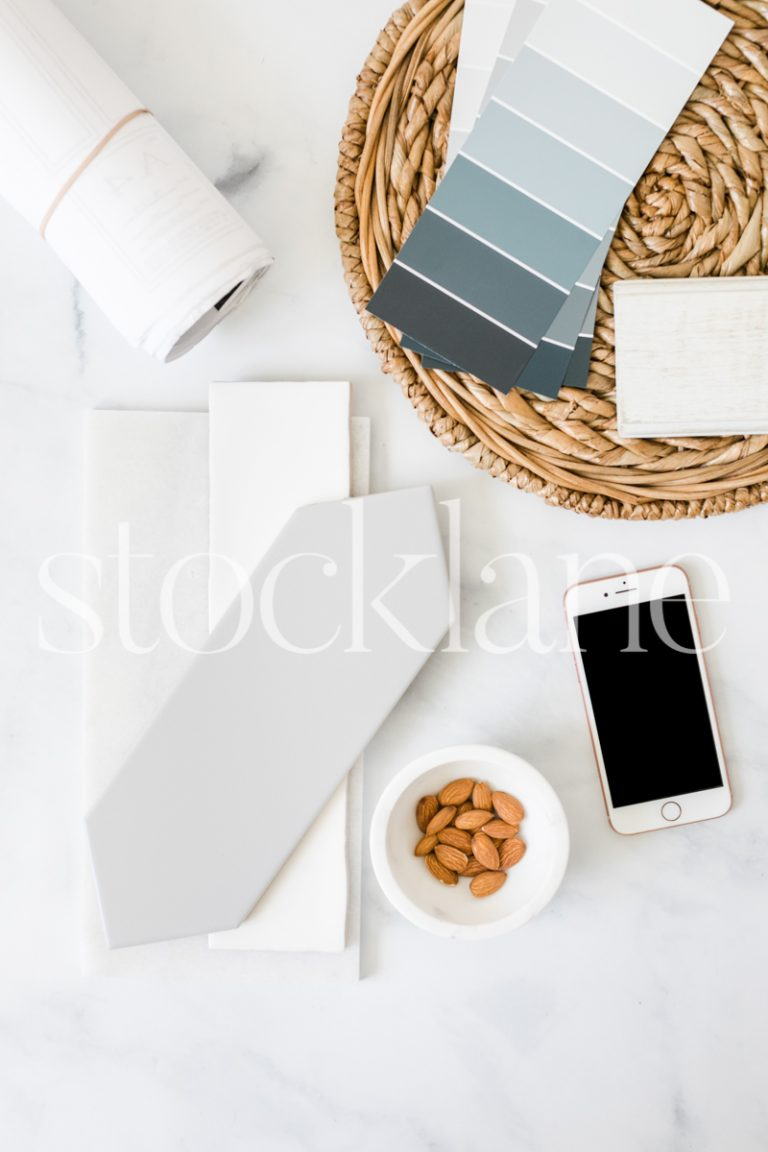 Vertical stock photo of a desktop with tile samples, color swatches and an iPhone