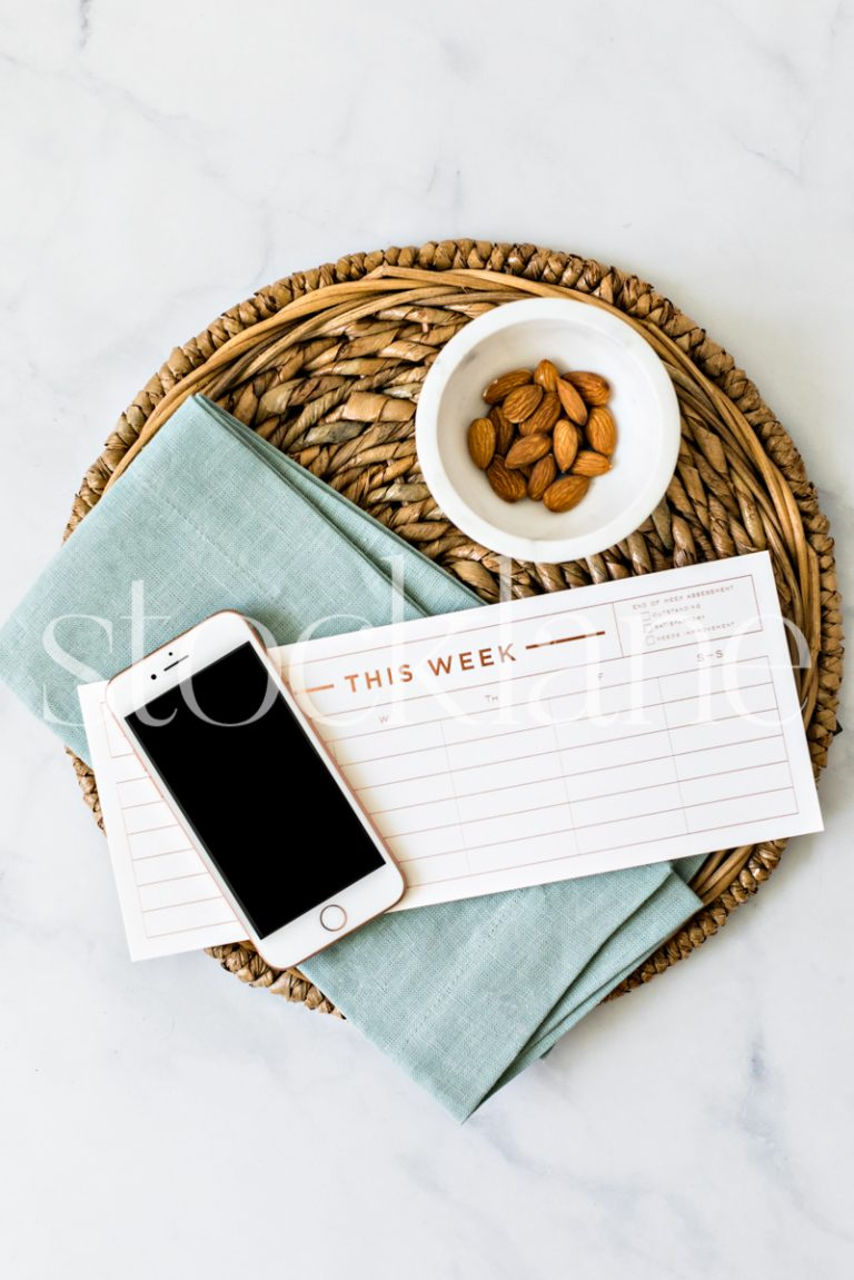 Vertical stock photo of a weekly planner and an iPhone