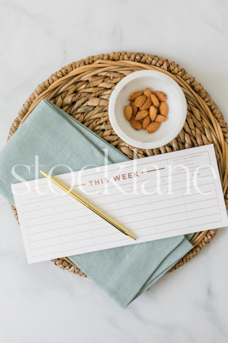 Vertical stock photo of a weekly planner and a bowl of almonds