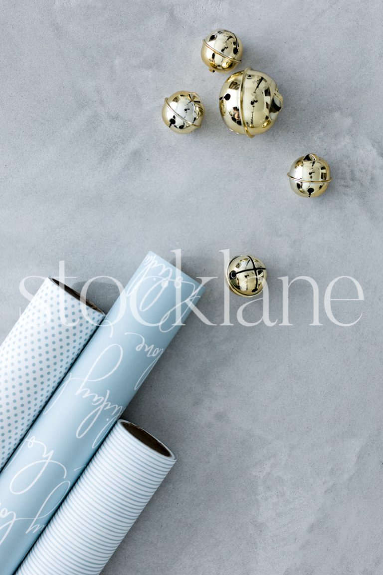 Vertical stock photo of light blue Christmas wrapping paper and bells