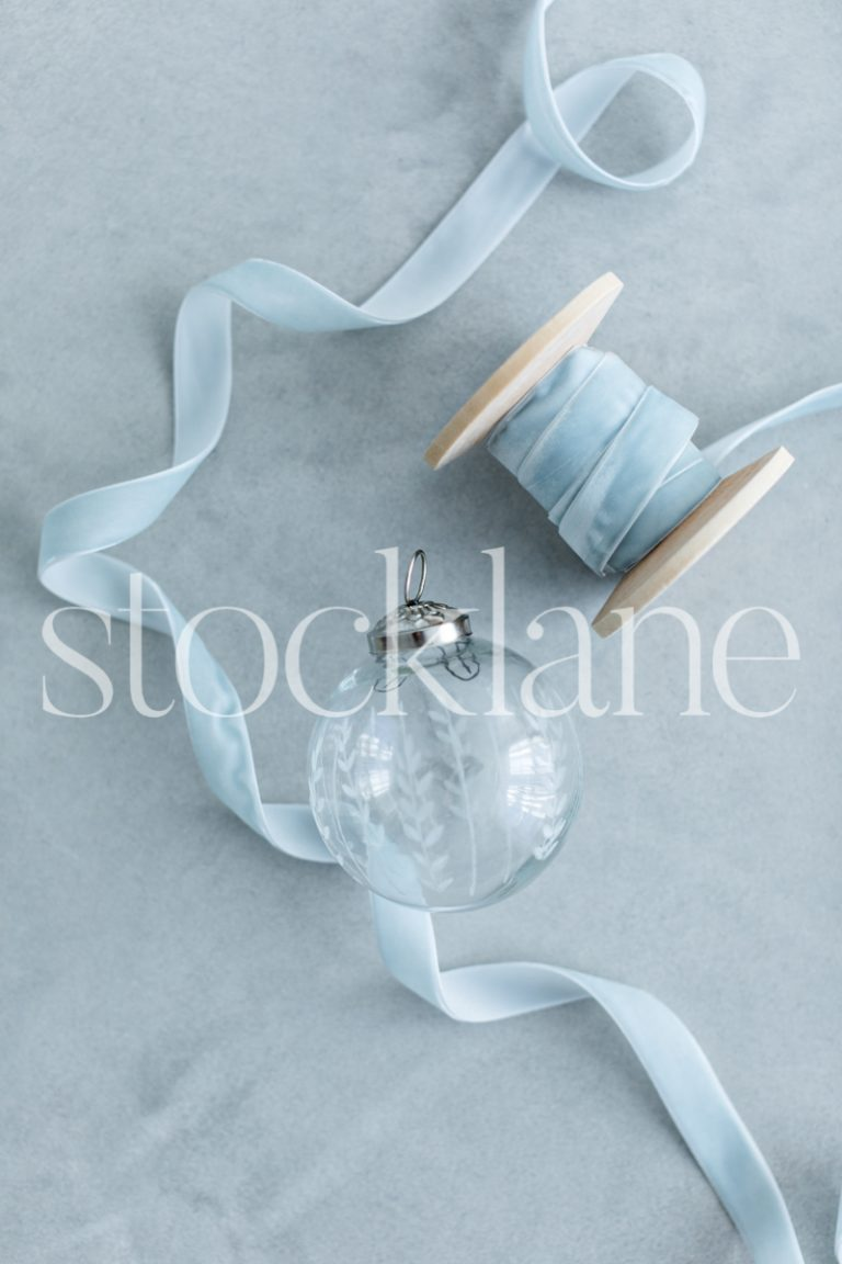 Vertical stock photo of glass Christmas ornament and light blue ribbon.
