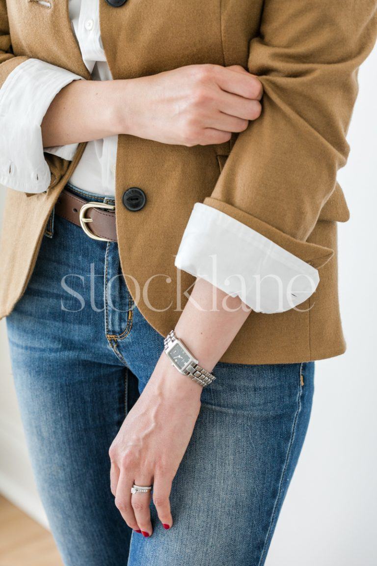 Vertical stock photo of woman pulling up the sleeve of her blazer.
